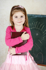 Little girl holding book and standing in front of the blackboard