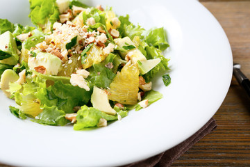 Fresh salad with avocado, lettuce, orange and crushed nuts