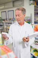 Senior pharmacist holding medicine and clipboard