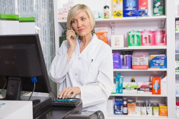 Blonde pharmacist using computer while phoning