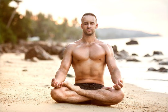 man practice yoga on the beach at sunset