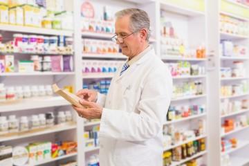 Smiling senior pharmacist reading prescription