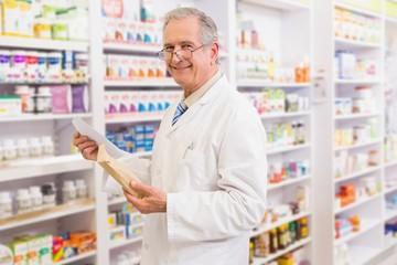 Smiling senior pharmacist holding envelope and prescription