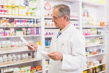 Senior pharmacist looking at medicine and prescription