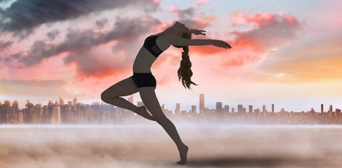 Composite image of side view of a sporty young woman stretching