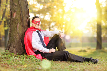Man in superhero outfit sitting in a park