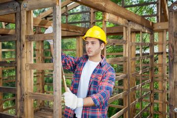 Worker Taking Measurements In Wooden Cabin
