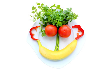 Funny face from vegetable and fruits on a white plate