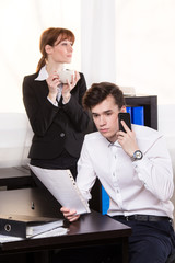 Business man call someone and business woman drinking coffee