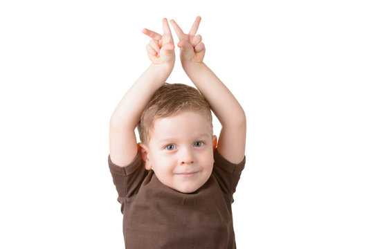 small boy showing victory sign on fingers