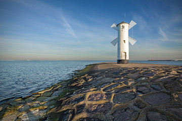 Sunrise on the coast, lighthouse windmill in Swinoujscie, Poland