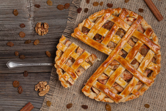 A piece of sliced apple pie with nuts on metal spatula on vintag