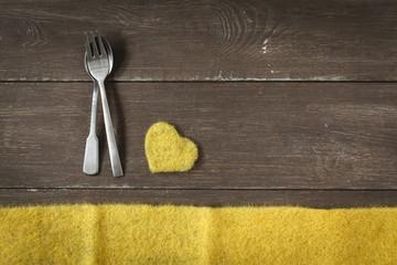 Besteck auf Holzuntergrund, gelbes Herz