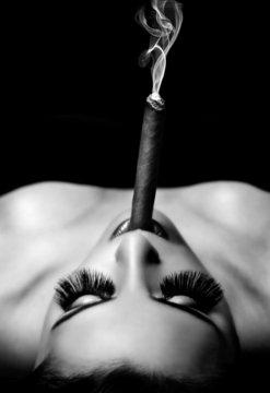 beautiful woman smokes a cigar