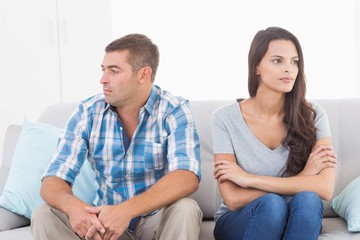 Couple looking away while sitting on sofa