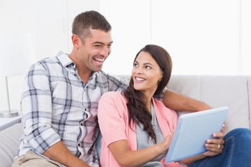 Couple with digital tablet sitting on sofa