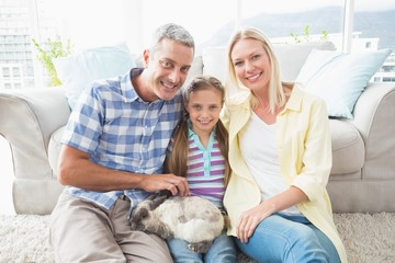 Happy parents and daughter with rabbit in living room