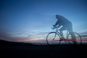 cyclist in motion blur in blue sky