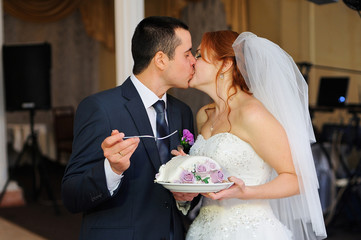 Bride and groom feed each other by wedding cake and kissing