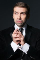 Closeup portrait of a young pensive businessman over dark backgr