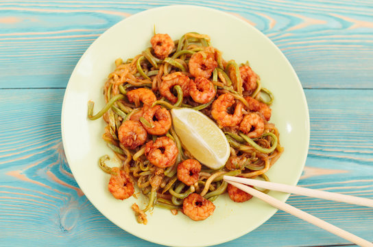 shrimps and zucchini noodles in green plate on blue table