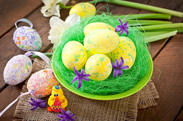 Easter eggs and flowers on wooden background