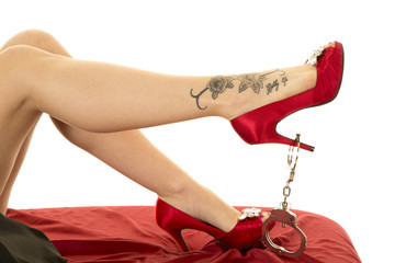 woman legs in red shoes with a tattoo and handcuffs