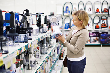 Woman chooses blender in store