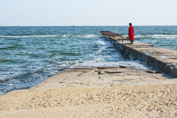 Girl standing on a pier looking into the distance