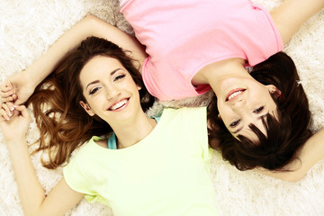 Two girls lying on fluffy white carpet, top view