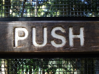 A wooden push sign panel  on door