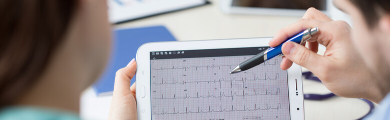 Modern cardiologists analyzing electrocardiogram
