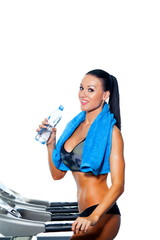 Smiling athletic woman drinking water on a treadmill.