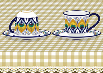 Two tea cups with saucer on checkered tablecloth