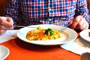 Rührei, ein Omelet liegt auf dem Teller. Ein Mann wird es mit Messer und Gabel verspeisen.