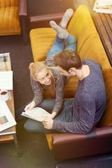 entspanntes paar liegt auf dem sofa und liest die zeitung