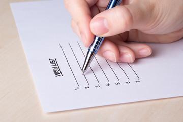 female hand writing her wish list