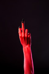 Red devil hand with black nails showing middle finger