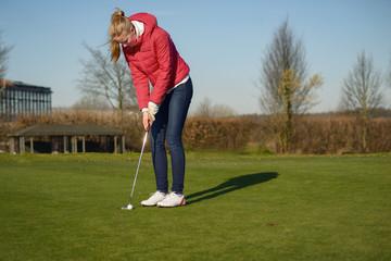 Junge Frau beim Putten auf Golf Grün
