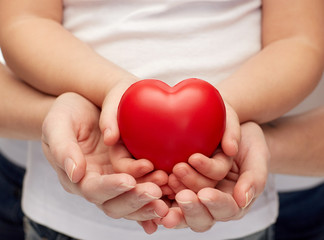 close up of woman and girl hands holding heart