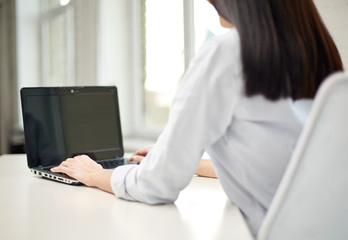 close up of woman typing on laptop at office