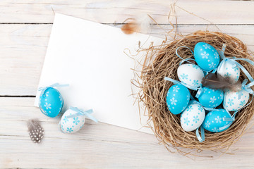Easter background with blue and white eggs in nest and greeting