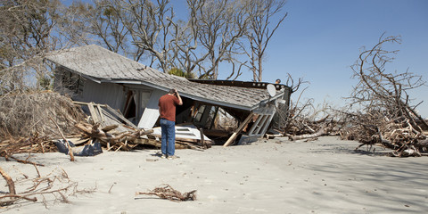 man grieving over destroyed house
