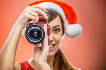 smiling woman in Santa Claus clothes with camera