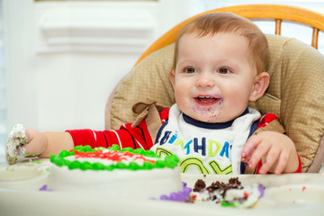 Happy baby boy eating cake for his first birthday party