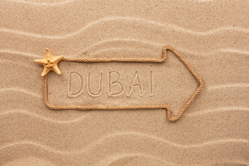 Arrow made of rope and sea shells with the word Dubai on the san