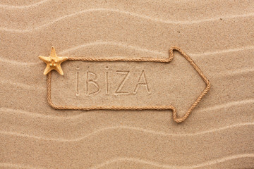Arrow made of rope and sea shells with the word Ibiza on the san