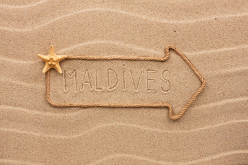 Arrow made of rope and sea shells with the word Maldives on the