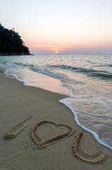 Poster Sea sunset I love you symbol written on sandy beach at sunset