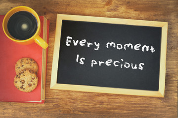 top view of blackboard with the phrase every moment is precious